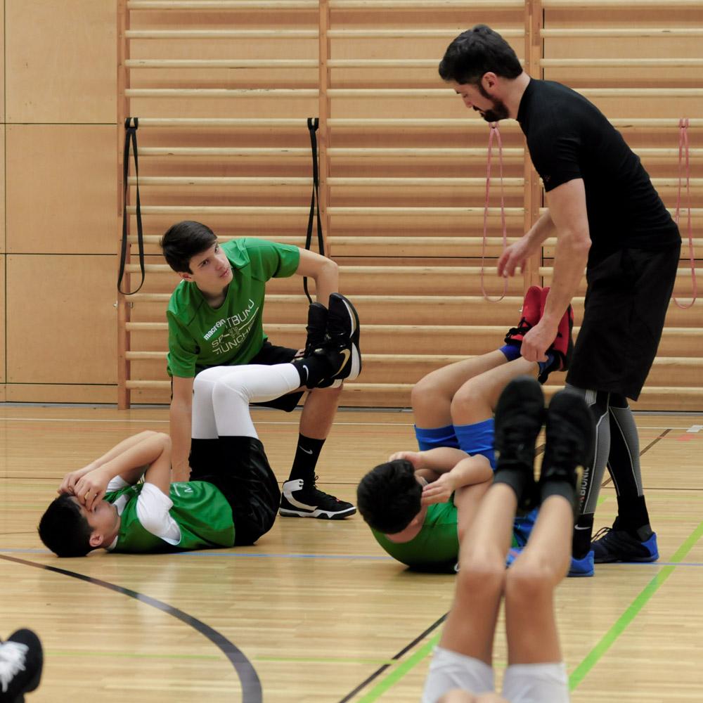 Nils Blond leitet die Basketballer bei der Partnerübung an
